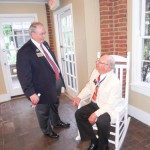 Patrick Tritt, left, Georgia district Kiwanis governor, and Charles Shepherd, seated, discuss Kiwanis history during the Sandy Springs Kiwanis Club's 60th birthday celebration on June16 at the Williams Payne Garden Room at Heritage Sandy Springs.