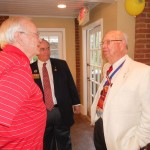 Hugh Lane of Roswell, left, Patrick Tritt, center, Georgia district Kiwanis governor, and Charles Shepherd, right, discuss Kiwanis history during the Sandy Springs Kiwanis Club's 60th birthday celebration on June16 at the Williams Payne Garden Room at Heritage Sandy Springs.