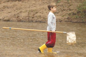 Spencer Gragg, 8, collects water samples from Nancy Creek on Jan. 12 to take to Oglethorpe University for further study. Spencer was with a group at the Blue Heron Nature Preserve in Buckhead that collected specimens to help gauge the health of the stream.