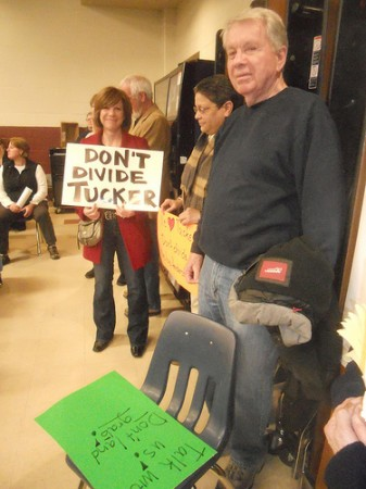 Hundreds packed the Tucker Middle School auditorium March 25 for a presentation on the creation of a new city of Lakeside. So many people attended the meeting that some were forced to sit on the auditorium stage to find a seat while another hundred stood in the back and along the sides of the auditorium. Some attending,  including Nicole Yarab, with sign, and Norm Lessard, right foreground, objected to a proposal to divide the Tucker community by placing part in the new city and part outside.