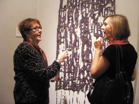 Mona Waterhouse, left, and  Linda King, right, discuss one of Waterhouse's works at the Spruill Gallery in Dunwoody.