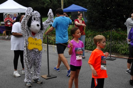 "Ahimsa the dog (actually organization executive director Maya Gupta in costume.), Bethany Patsios, center, and brother brother Ethan Patsios watch for the Patsios' father, Jordon, to complete the ""Wag and Walk"" fundraising run on Aug. 24 at Lenox Park in Brookhaven."