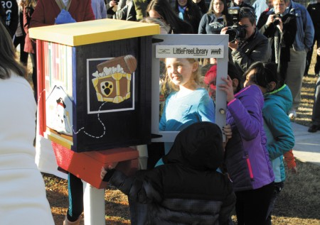 "Arwen Coy, 9, takes a peek into the ""little free library"" unveiled at Briarwood Park on Jan. 16. The Cross Keys Foundation, a public charity that supports education in the Brookhaven area, was instrumental in opening the free library, which features a post-mounted, book swap unit."