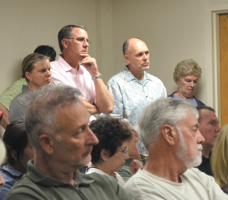 Manget Way homeowners Mark Collins, with hand to chin, and Larry Gluth, in blue shirt, listen to the discussion at the Dunwoody Homeowners Association April 13 meeting.