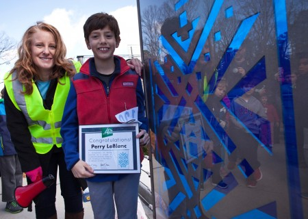 Livable Buckhead executive director Denise Starlings and fifth grader Perry LeBlanc pose with the panel based on his design.