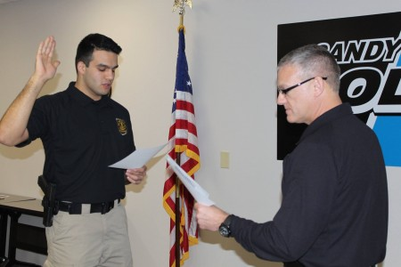 Will Oppermann, at left, is sworn in as a Sandy Springs police officer by Police Chief Ken DeSimone in January.
